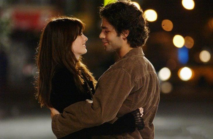 Escena de la película el diablo viste a la moda pareja de novios abrazados en medio de la calle