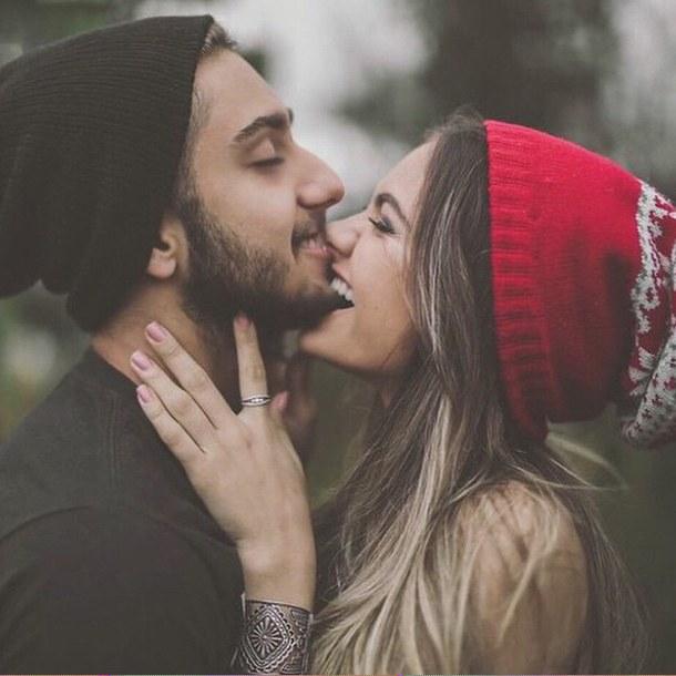 chic besando la barbilla de un chico mientras están en el bosque