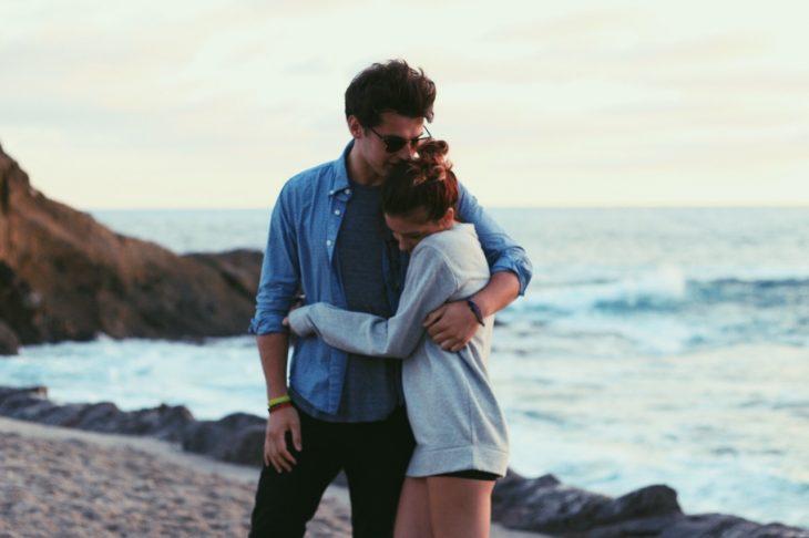 Pareja de novios abrazados mientras están frente al mar