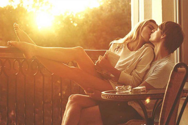 Pareja de novios sentados en una silla mientras se están besando al atardecer