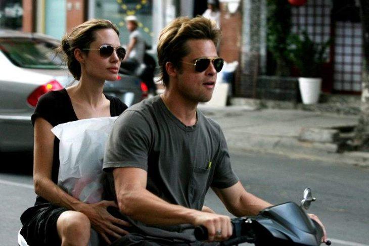 Brad pitt y angelina jolie en una motocicleta cianjando por las calles de una ciudad