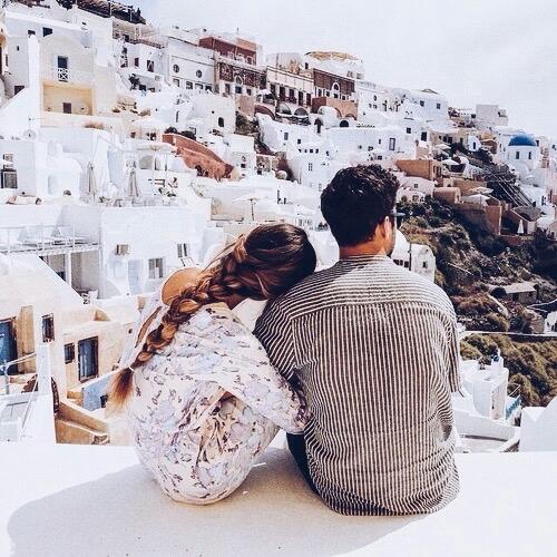 Pareja de novios abrazados mientras estàn viendo la ciudad