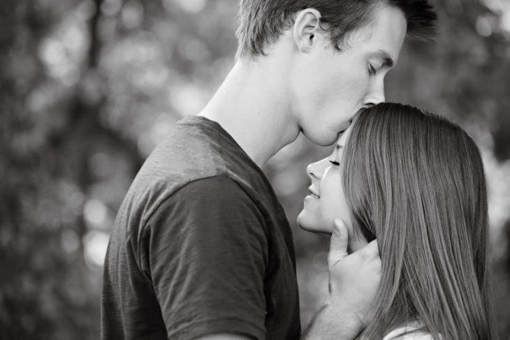 Chico besando la frente de una chica mientras la esta abrazando