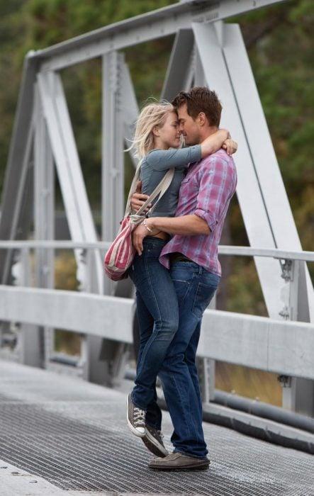 Chica y chico abrazados mientras estan en medio de un puente