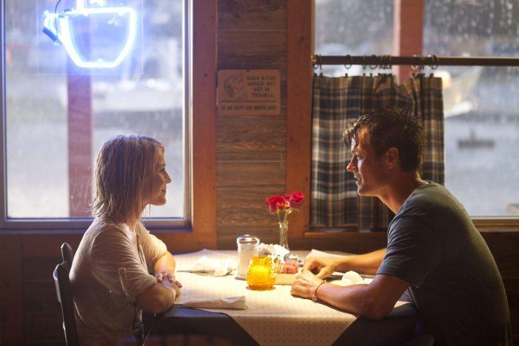 Escena de la película Safe Haven protagonistas hablando mientras estan sentados frente a un mesa hablando