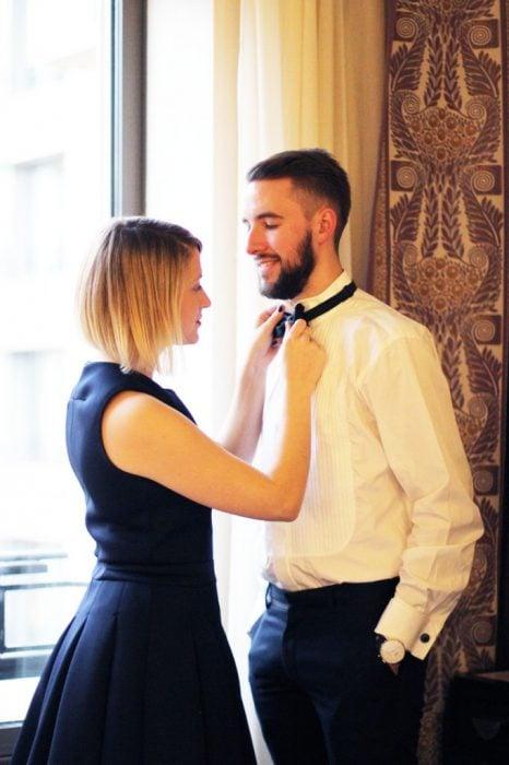 Chica arreglándolo la corbata a un chico