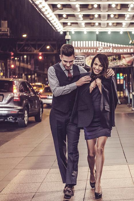 Hombre poniendole una chaqueta a una chica mientras camian por la calle