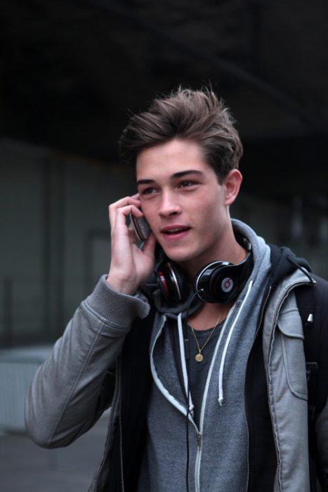 Chico hablando por celular mientras camina por la calle