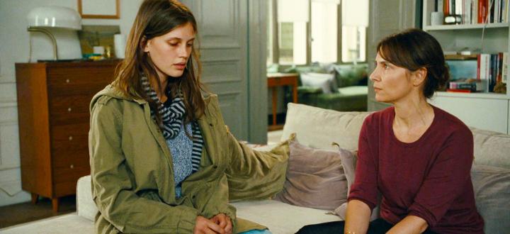 Madre e hija sentadas en el sofá conversando
