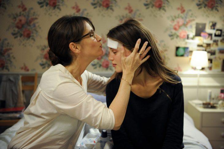 Escena de la película joven y bonita, madre besando la frente de su hija