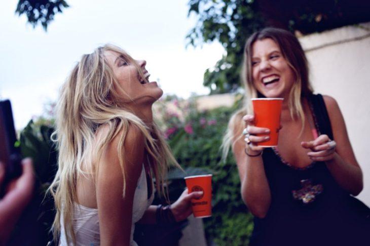 Chicas bebiendo de un vaso rojo y riendo muy contentas