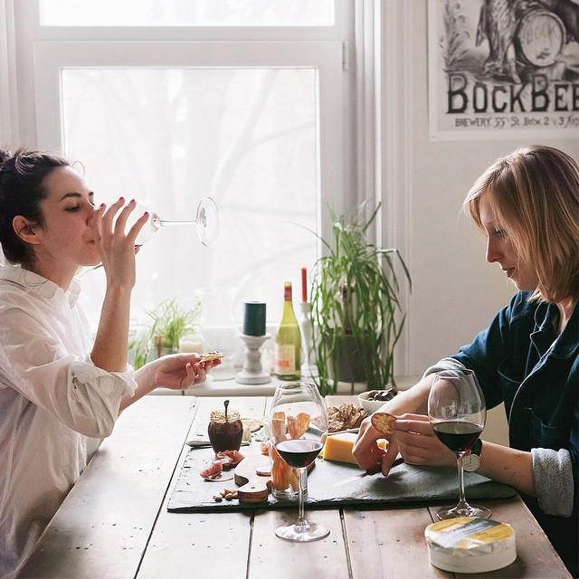 Chicas comiendo y bebiendo vino durante una cena