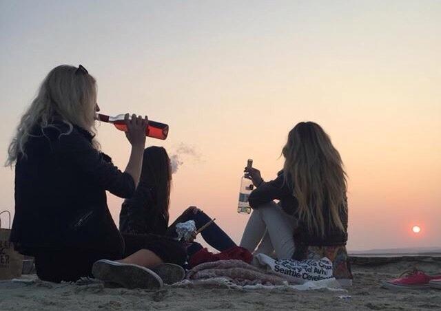 Chicas en la playa sentadas bebiendo