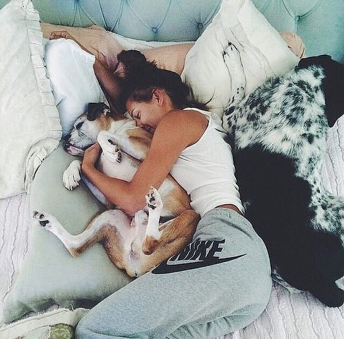 chica acurrucada con perro en cama