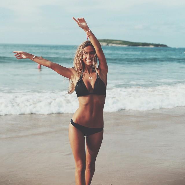 Chica en la playa sonriendo mientras levanta los brazos