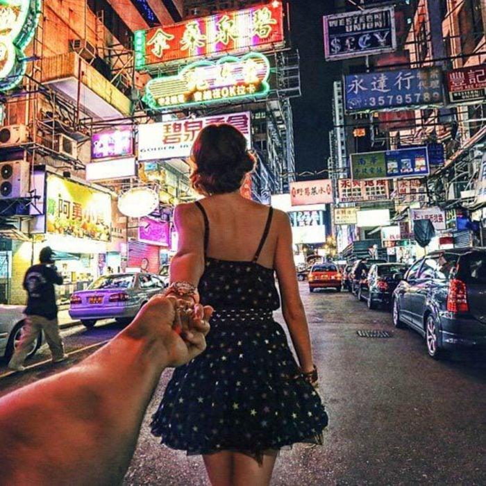 Chica caminando mientras es tomada de la mano de su pareja desde atrás