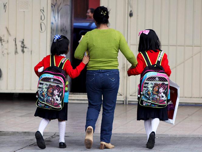 Niñas caminando de la mano de su mamá mientras van cargando mochilas para la escuela