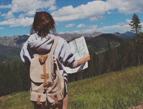Chica con un mapa en las manos mientras está parada en las montañas