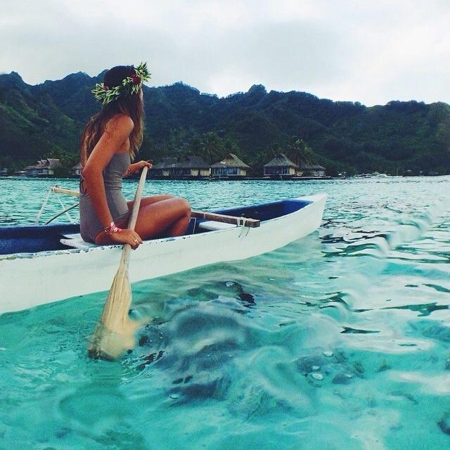 Chica sobre un kayak remando por el mar azul
