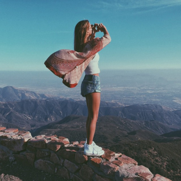 Chica parada sobre una pared de piedra viendo con unos binoculares a lo lejos
