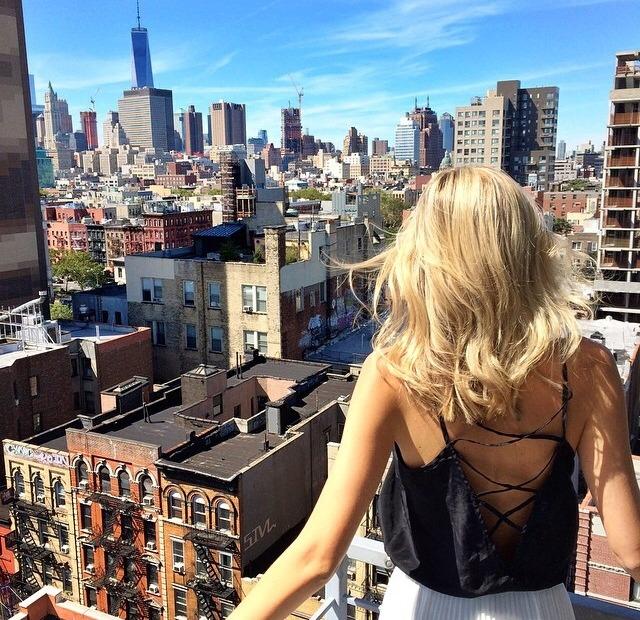 Chica parada en un edificio viendo la ciudad