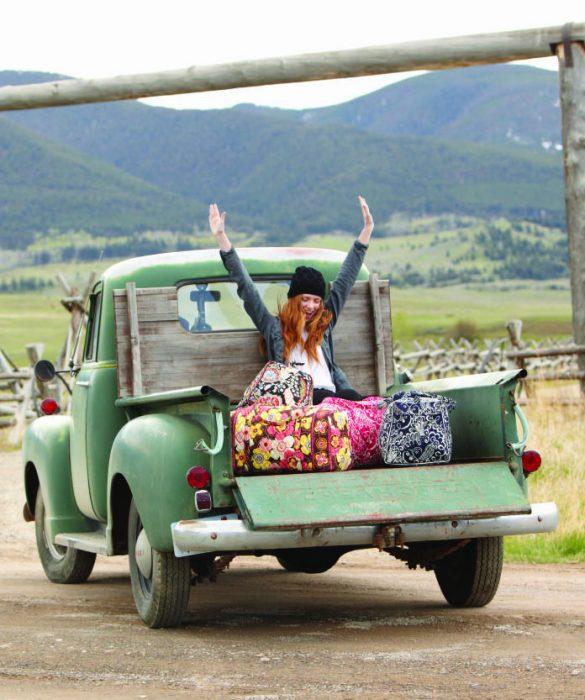 Chica sentada en la parte trasera de una camioneta con maletas y levantando los brazos