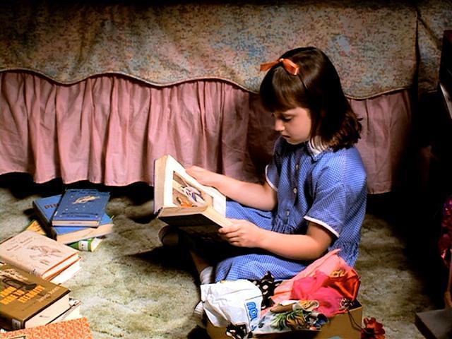 Niña de la película matilda leyendo sobre la alfombra de su cuarto