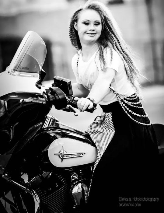 Modelo con sindrome de down sobre una motocicleta posando para una fotografía