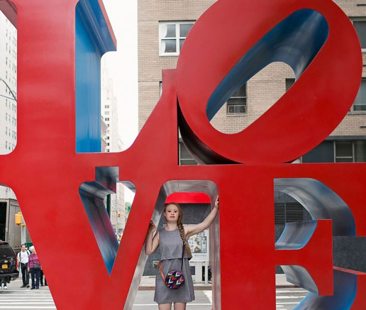 Modelo con sindrome de down parada sobre unas letras que dicen love en la ciudad de nueva york