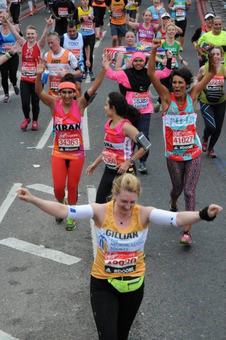 Mujer corriendo un maratón al lado de sus compañeras