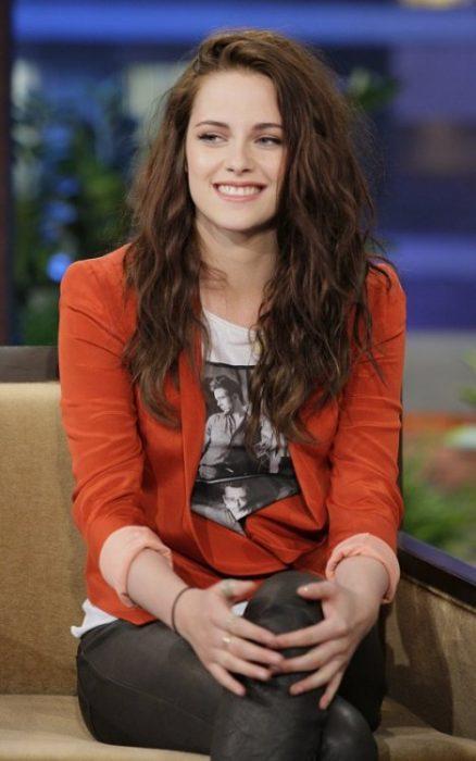 Kristen Stwart sentada en un sofá sonriendo
