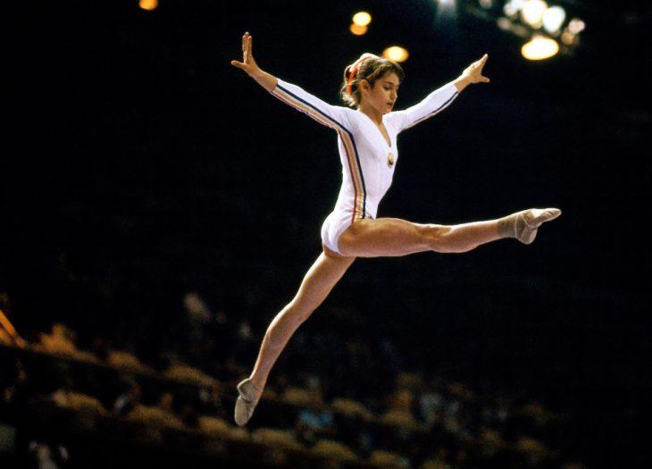 Nadia Comaneci haciendo un salto en gimnasia