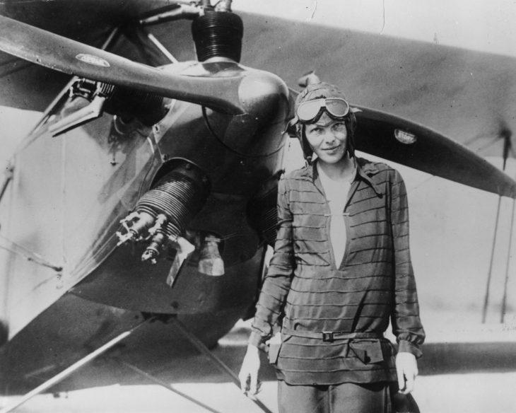 Amelia Earhart parada frente a un avión en el cual volaba