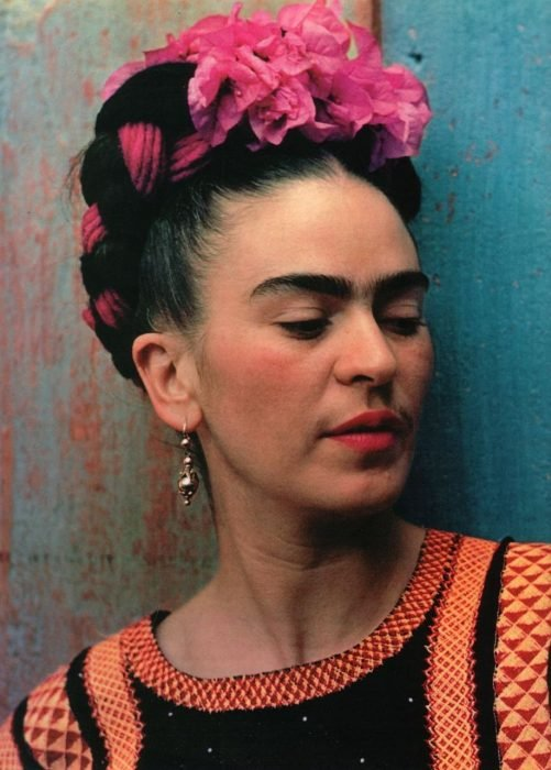 artista Frida khalo recargada sobre una pared de color azul