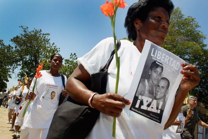 mujer de la organización las damas de blanco caminando por la calle exigiendo justicia