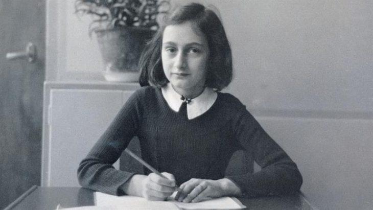 niña Ana frank sentada escribiendo en su diario