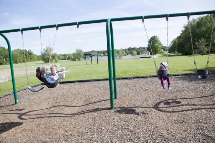 Niños jugando en los columpios en un parque