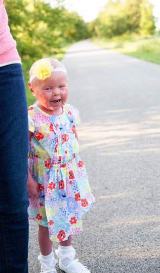 Niña usando un vestido de flores mientras está parada junto a su mamá en la calle