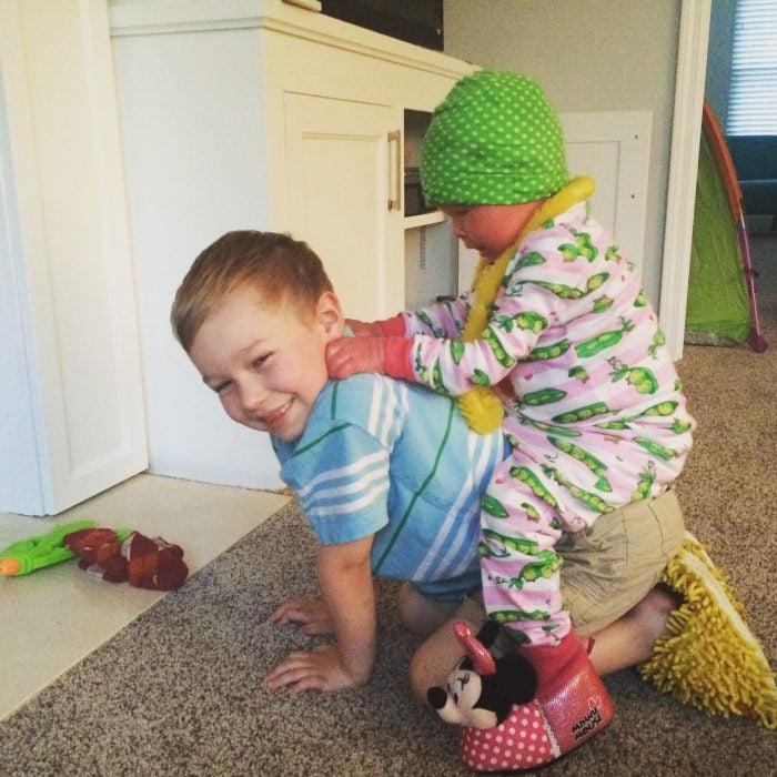Niño cargando a su pequeña hermana en la espalda mientras juegan en una habitación