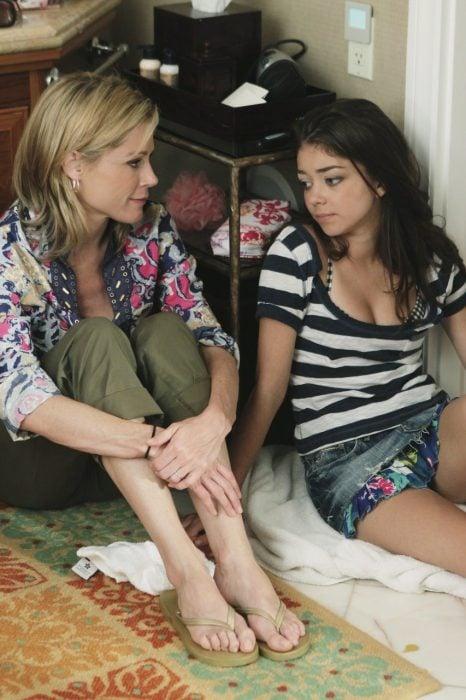 Chica hablando con su madre mientras están sentadas en el suelo