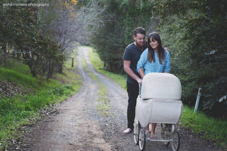 Pareja de novios parados sobre un camino de tierra empujando el coche de un bebé