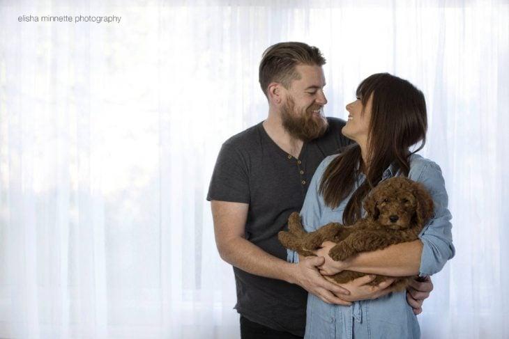 Pareja de novios sosteniendo en sus brazos a un cachorro