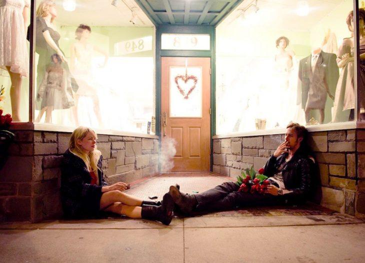 Escena de la película blue valentine pareja fumando afuera de una tienda