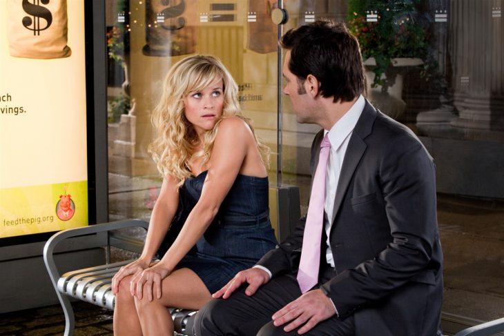 rese whiterspon sentada en una banca de autobus hablando con un hombre