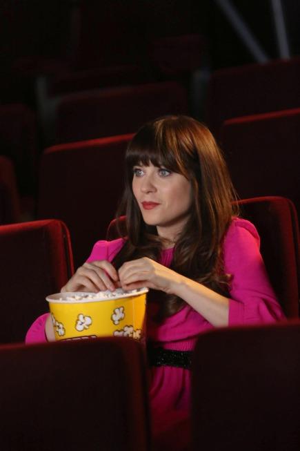 New Girl: Jess sentada en una sala de cine viendo una película y comiendo palomitas