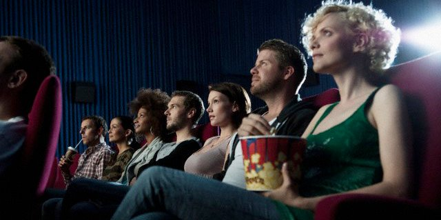 Personas viendo una película en una sala de cine mientras comen palomitas