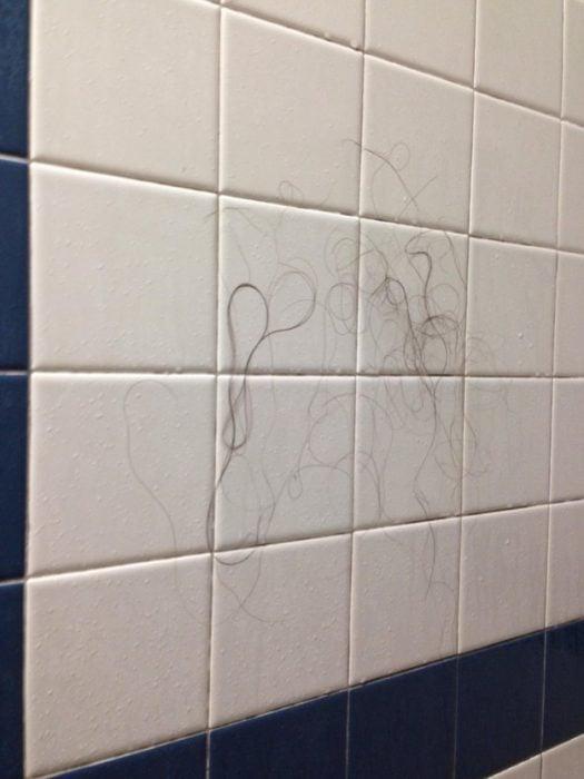 pared del cuarto de la ducha con cabellos pegados por el agua