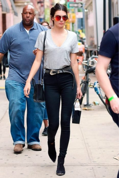 Chica vestida de negro y gris usando un cinturon y cargando una bolsa de regalo mientras camina por las calles