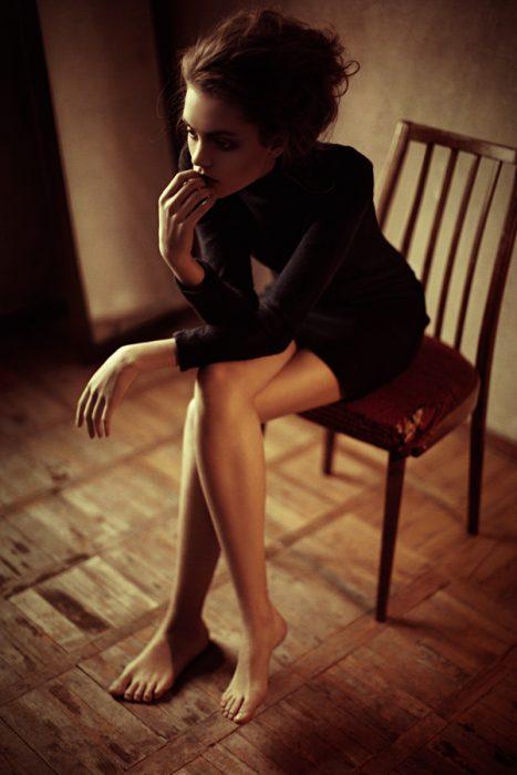 Chica sentada en una silla de manera incomoda