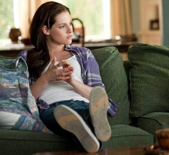 Escena de la película eclipse kristen stwart sentada en un sofá
